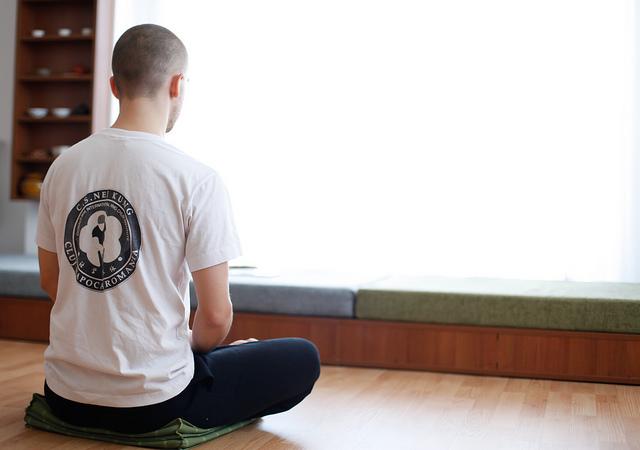 Un homme fait du yoga assis dans son salon